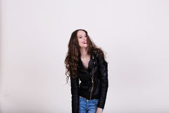 Beautiful girl laughing. Beautiful girl in black leather jacket laughs on a white background Stock Photos