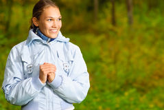 Beautiful girl laughs. Young woman in blue jacket looks aside and smiles in autumn wood Stock Image