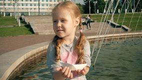 Beautiful girl launches paper boats in a fountain. 4k stock video footage