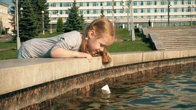 Beautiful girl launches paper boats in a fountain stock video