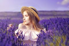 Beautiful girl on the lavender field. Beautiful woman in the lavender field on sunset. Soft focus. Provence, France. A girl in pin. K dress and hat walking royalty free stock photos