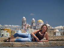 Beautiful girl laying. Cathedral of Cadiz, Spain, on the background Stock Photography