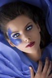 Beautiful girl laying between blue satin sheets Royalty Free Stock Photo