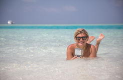 Beautiful girl is laying in blue waters of Indian ocean with telephone Royalty Free Stock Photos