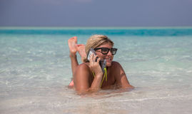 Beautiful girl is laying in blue waters of Indian oceanand speaking by telephone Royalty Free Stock Photos