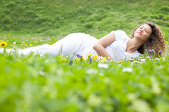 Beautiful girl laying on flowers field,outdoor summer Stock Images