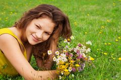 Beautiful girl laying on grass with bouquet Stock Images