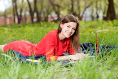Beautiful girl laying on the grass with a notebook Royalty Free Stock Images