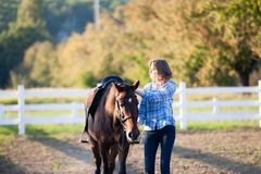 Beautiful girl with horse. Beautiful girl leading her brown horse at the farm Royalty Free Stock Photos