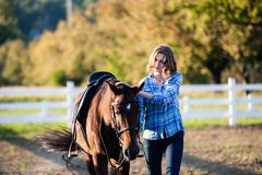 Beautiful girl with horse. Beautiful girl leading her brown horse at the farm Royalty Free Stock Image