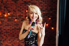 Beautiful girl leading holding a microphone and smiling royalty free stock image