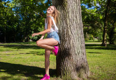 Beautiful girl leaning against tree laughing Stock Photo