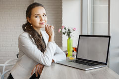 Beautiful girl leans her elbows on table with laptop Royalty Free Stock Images