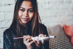 Beautiful girl in leather jacket doing makeup. Beautiful young woman putting makeup Stock Images