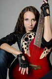 Beautiful girl in a leather jacket with a guitar Royalty Free Stock Photography