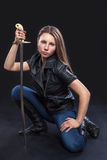 Beautiful girl in leather jacket with sword on black background. Beautiful, brown-haired woman militant in leather jacket with a sword on a black background stock image