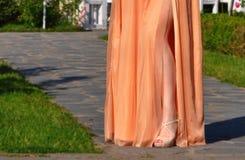 Beautiful girl leg in gold long dress. Detail of beautiful girl leg in gold long dress stock photo