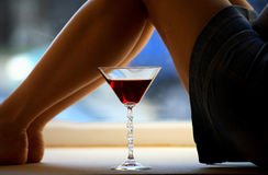 Beautiful girl legs and a glass Royalty Free Stock Photo