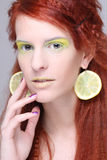 Beautiful girl with lemon slices in ears Stock Photos