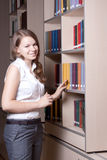 Beautiful girl in the library. Among the books Stock Photo