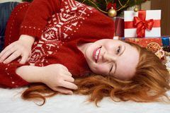 Beautiful girl lie in christmas decoration. Home interior, fir tree and gifts. New year eve and winter holiday concept. Stock Images