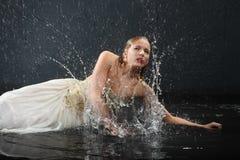 Beautiful girl lies on floor and sprays water stock image