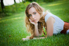 Beautiful girl lies on the grass stock images