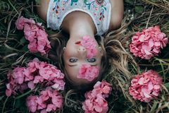 A beautiful girl lies on the ground with flowers on her face and in her hair royalty free stock photos