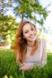 Beautiful girl lies on lawn Royalty Free Stock Image