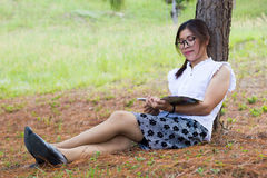 Beautiful girl lies on meadow and reads the book Royalty Free Stock Photo