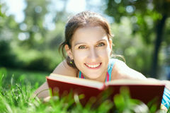 Beautiful girl lies on meadow and reads the book Royalty Free Stock Images