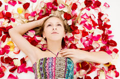 Beautiful girl lies in the petals of roses Royalty Free Stock Photo
