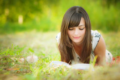 Beautiful girl lies and reads Stock Image