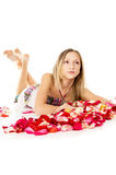 Beautiful girl lies in rose petals Royalty Free Stock Image
