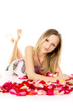 Beautiful girl lies in rose petals Stock Photos