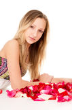 Beautiful girl lies in rose petals Stock Photography