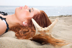 The beautiful girl lies on sea coast with shells nature vacation Royalty Free Stock Image