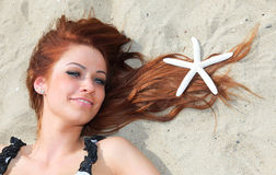 The beautiful girl lies on sea coast with shells nature vacation Royalty Free Stock Images