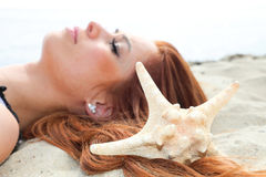 The beautiful girl lies on sea coast with shells nature vacation Stock Photo