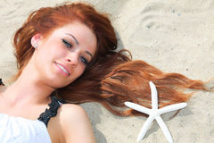 The beautiful girl lies on sea coast with shells nature vacation Stock Photos