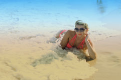 The beautiful girl lies in sea waves, a blue background Royalty Free Stock Photo