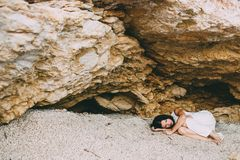 Beautiful girl lies in a stone canyon on the beach Stock Images