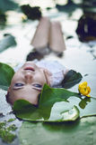 Beautiful girl lies in the water among the flowers Royalty Free Stock Image