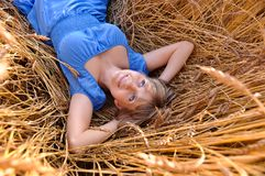 Beautiful girl lies in wheat Stock Image