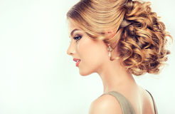Beautiful girl light brown hair with an elegant hairstyle. Hair wave ,curly hairstyle royalty free stock image