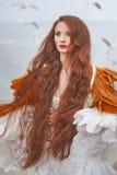 Beautiful girl like a swan on the beach royalty free stock photos