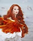 Beautiful girl like a swan on the beach. Beautiful girl with red hair walking along the seashore. winter photos Stock Image