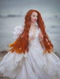 Beautiful girl like a swan on the beach royalty free stock photo