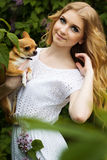 Beautiful girl with lilac flowers and her chuhuahua dog. Beautiful blonde girl with a lilac flowers and small chuhuahua dog Stock Photo