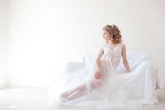 Beautiful girl in lingerie sitting on a white couch wedding Royalty Free Stock Image